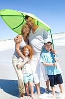 Parents and two children on the beach, posing for the camera, outdoors