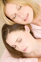 Portrait of two women with eyes closed, indoors