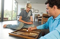 Father and son playing backgammon, indoors