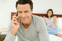 Portrait of a man phoning with cell, woman sitting on bed in background, indoors