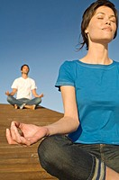 Couple in yoga attitude, outdoors (thumbnail)