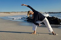 Young woman stretching on the beach, outdoors