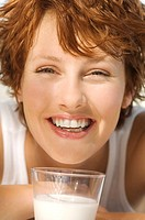 Portrait of a young smiling woman, glass of milk (thumbnail)