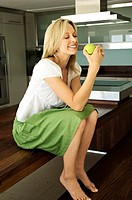 Young smiling woman eating an apple