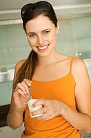 Young smiling woman eating yogurt
