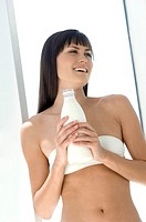 Young smiling woman holding bottle of milk