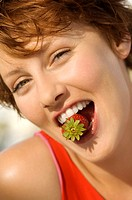 Portrait of a young woman holding strawberry between her teeth