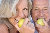 Portrait of smiling couple eating apples