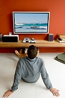 Man watching TV sitting on floor