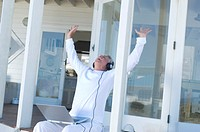 Man listening to music with laptop, arms in the air