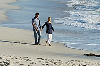Couple holding hands, walking on the beach