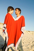 Couple on the beach, sharing a poncho (thumbnail)