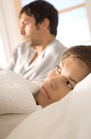 Couple in bed, sulking woman in foreground (thumbnail)