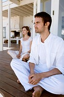 Couple sitting cross-legged on wooden terrace