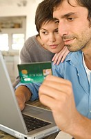 Young couple using credit card on internet