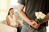 Man hiding bunch of flowers behind his back, facing smiling woman