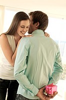 Man hiding gift behind his back, facing smiling woman