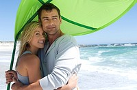 Couple embracing on the beach, beach umbrella