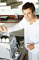 Young smiling man in front of espresso maker