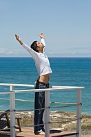 Young man stretching on terrace, sea in background