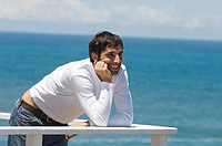 Young smiling man leaning against balustrade, sea in background