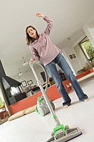 Woman vacuuming while listening to MP3 player