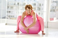 Young smiling woman resting on big pink ballon
