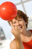 Portrait of young woman balancing red balloon on her finger