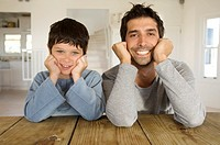 Father and son smiling for the camera, with hands on cheeks