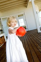 Little girl holding red ball on wooden terrace