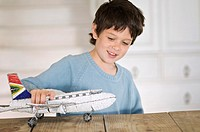 Little boy playing with model aeroplane