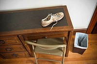 Man's sneaker on top of a desk in a bedroom