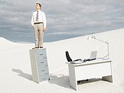 A businessman in the middle of nowhere on his filing cabinet