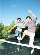 Friends jumping over a tennis net