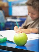 A student with an apple on his desk