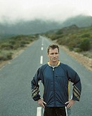 A stoic man standing on a desolate road