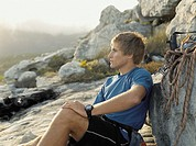 A mountain climber sitting down resting