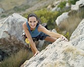 A woman climbing a mountain smiling