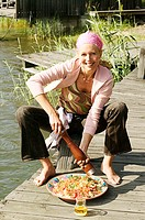 Young woman sitting on landing stage seasoning couscous salad