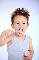 Small boy eating fruit yoghurt