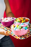 Hands holding a tray of assorted sweets in bowls