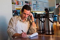 Male store clerk using a cordless phone and checking inventory
