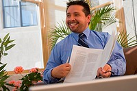Real estate agent holding a document and smiling