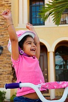 Close-up of a girl laughing with her arms raised