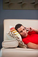 Side profile of a young man talking on a mobile phone and lying on a couch