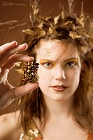 Woman dressed up as autumn holding a pinecone