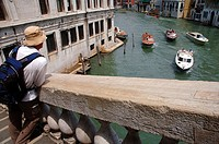 Tourist watching boat traffic on the Grand Canal from the Rialto Bridge, Venice, Italy