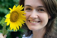 Young Woman Smiling and Holding a Sunflower