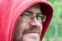 Young Man With Beard Wearing Glasses and Red Hood Looking into Distance