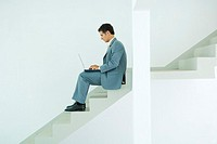Man sitting on stairs, using laptop